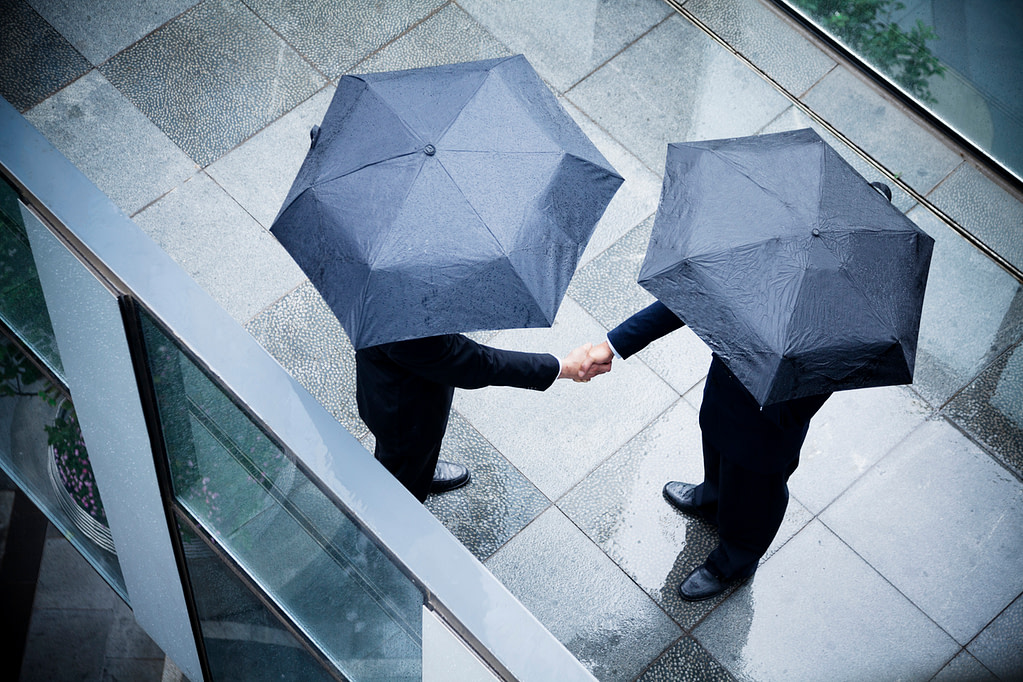 Two businessmen holding umbrellas and shaking hands outside